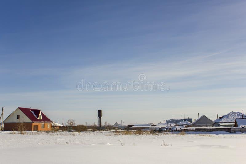 Torre de água e casas modernas da vila sob um céu azul com as nuvens brancas no inverno imagens de stock royalty free