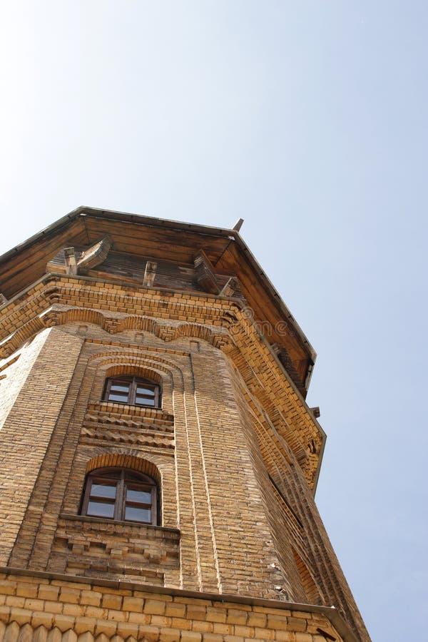 Torre de água velha que constrói a parte superior europeia amarela da torre da arquitetura da parede de tijolo no fundo do céu az imagem de stock royalty free