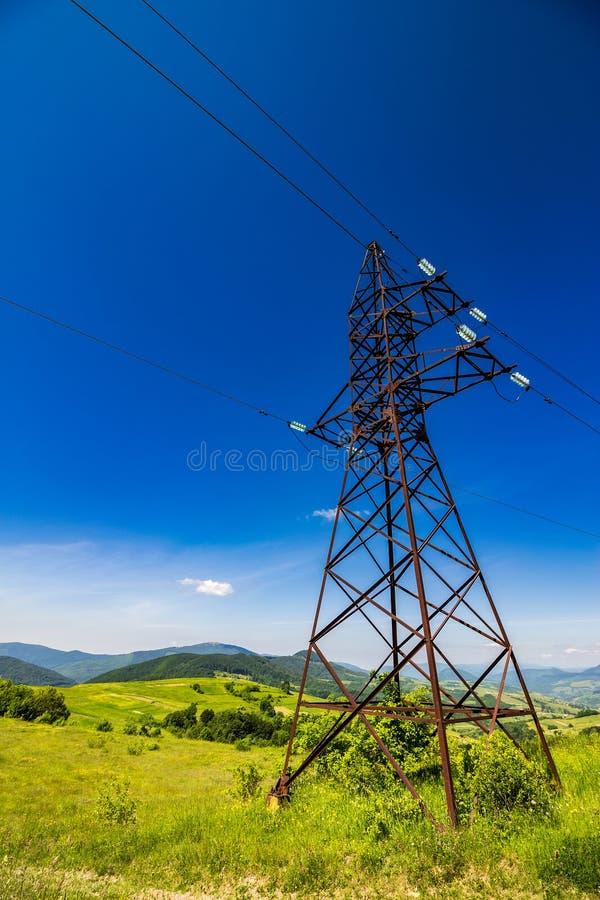 Torre de alto voltaje de las líneas eléctricas en montañas foto de archivo