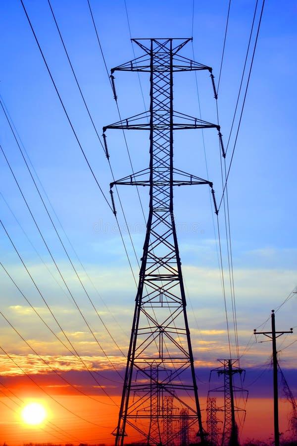 Torre de alto voltaje eléctrica de la transmisión en la puesta del sol imágenes de archivo libres de regalías