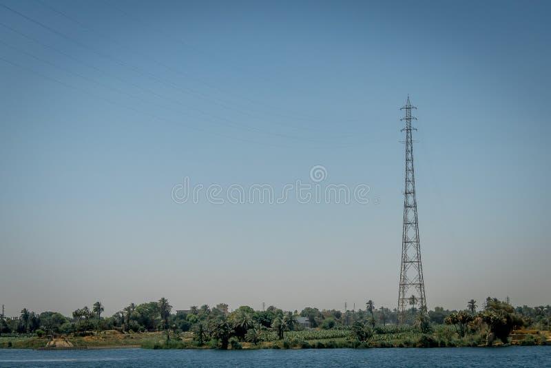 Torre de alto voltaje en el banco del río Nilo Egipto imagenes de archivo