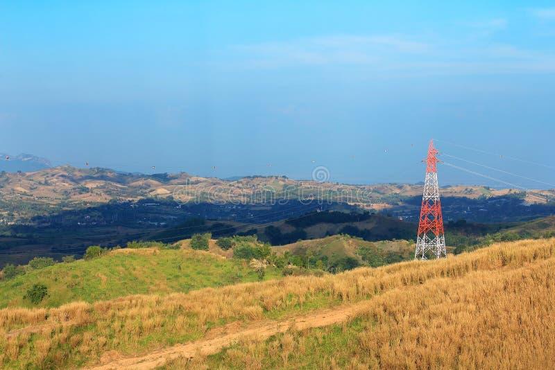 Torre de alto voltaje en la montaña con el prado, los polos eléctricos y los cables en zonas rurales fotos de archivo libres de regalías