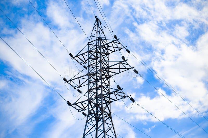 Torre de alto voltaje Pilones de un poder del alto voltaje contra el cielo azul imagenes de archivo