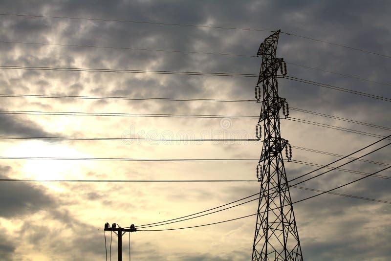 Torre de alto voltaje y pequeño poste eléctrico fotos de archivo libres de regalías