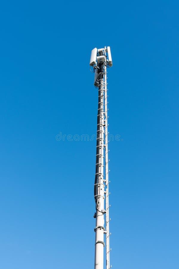 Torre de antena alta para o serviço telefônico móvel e celular com um fundo do céu azul fotografia de stock