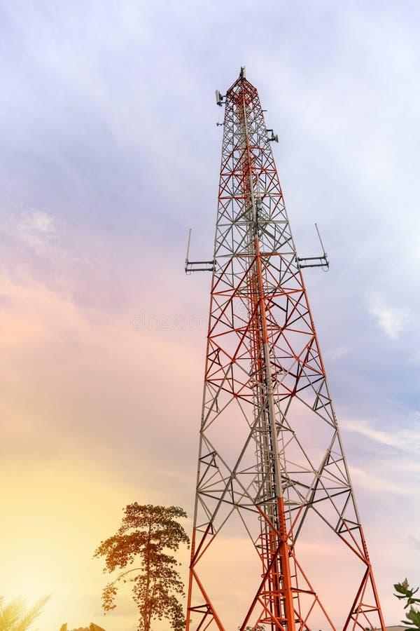 Torre de antena del repetidor de la comunicación del teléfono móvil y de la señal de la red con el fondo del cielo azul Efecto lu fotografía de archivo