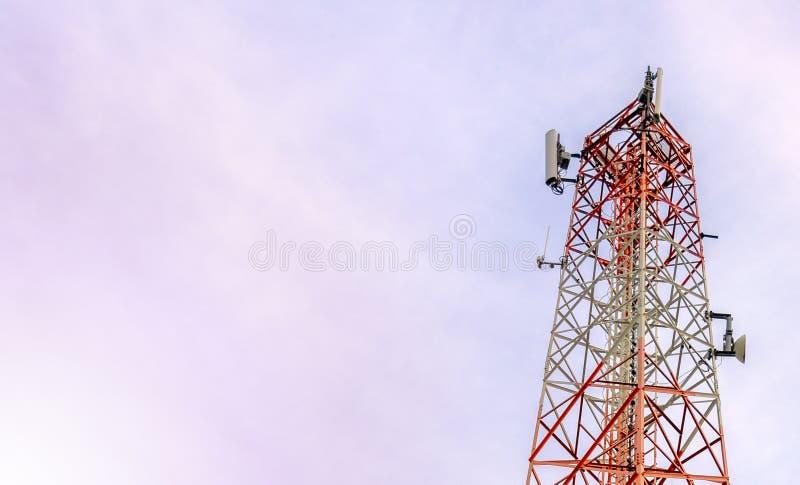Torre de antena del repetidor de la comunicación del teléfono móvil y de la señal de la red con el fondo del cielo azul r imagenes de archivo