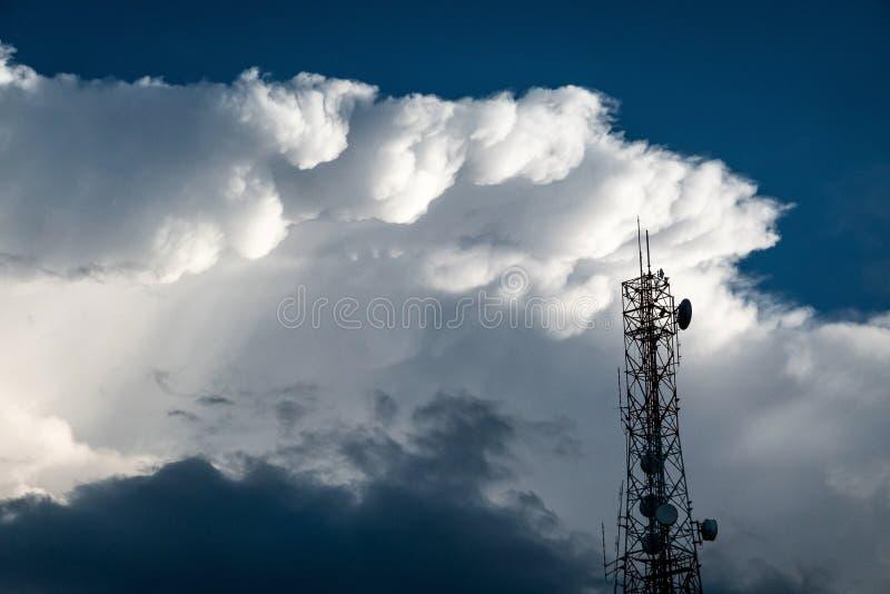 Torre de antena e repetidor de uma comunicação com as nuvens macias brancas no fundo do céu azul foto de stock royalty free