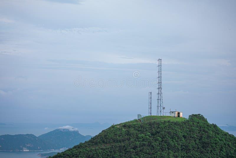 Torre de antena en un pico de una colina imagenes de archivo