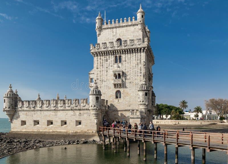 Torre de Belem contra el cielo azul, una cola de turistas en la entrada fotos de archivo libres de regalías