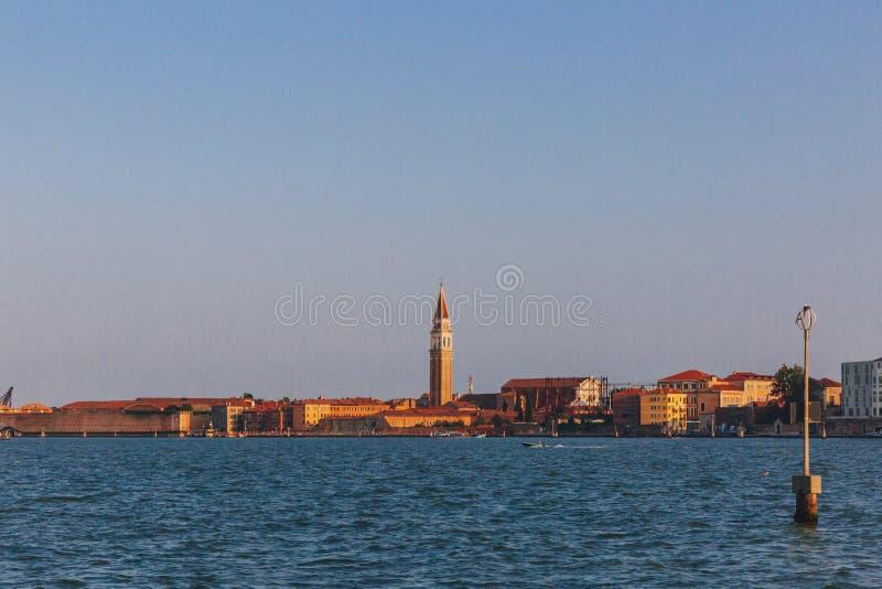 Torre de Bell sobre as casas Venetian pela água no por do sol, em Veneza, I foto de stock