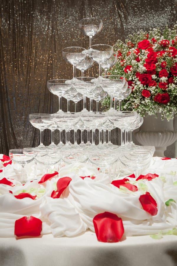 Torre de Champagne e rosas vermelhas bonitas na cerimônia de casamento fotografia de stock royalty free