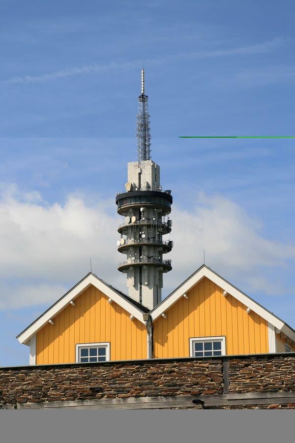 Torre de comunicação e casas de madeira fotografia de stock