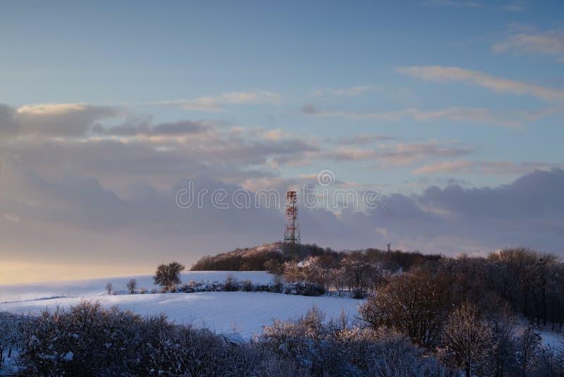 Torre de comunicación del transmisor en paisaje del invierno imagen de archivo