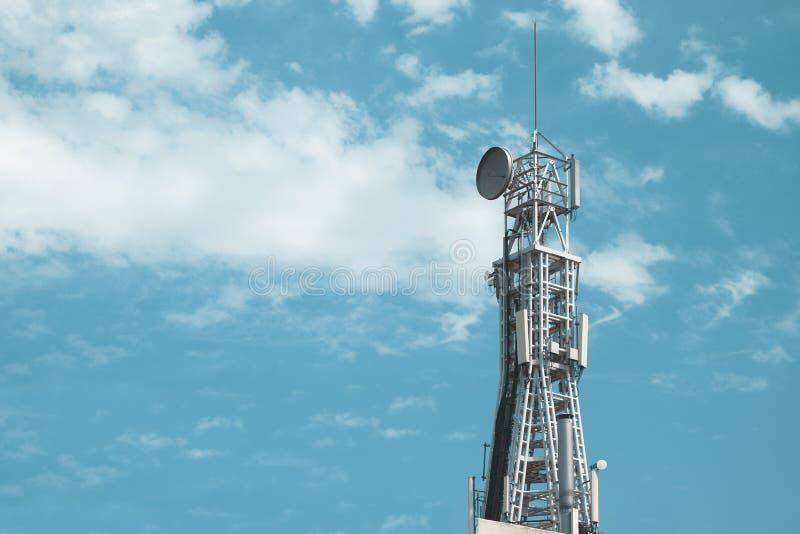 Torre de comunicación móvil de la señal de las telecomunicaciones contra un cielo azul espacio vac?o de la copia imagenes de archivo