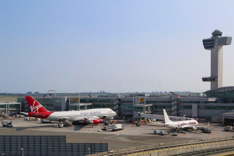 Torre de controlador aéreo y terminal 4 con Virgin Atlantic Boeing 747 y Caribbean Airlines Boeing 737 en las puertas en JFK fotos de archivo