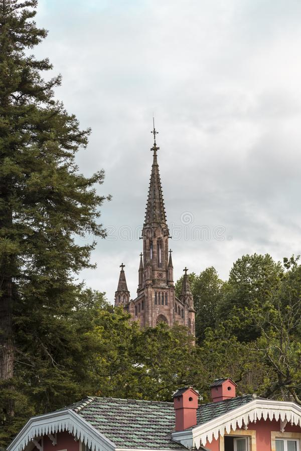Torre de elevarse de iglesia entre los árboles foto de archivo