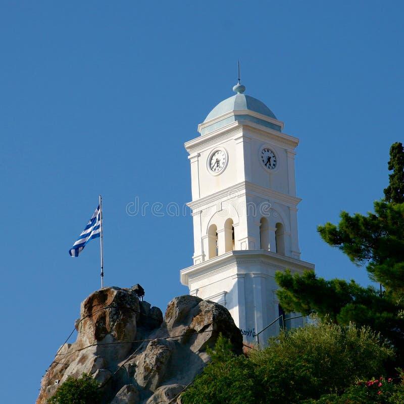 Torre de iglesia blanca y bandera griega contra el cielo azul fotografía de archivo