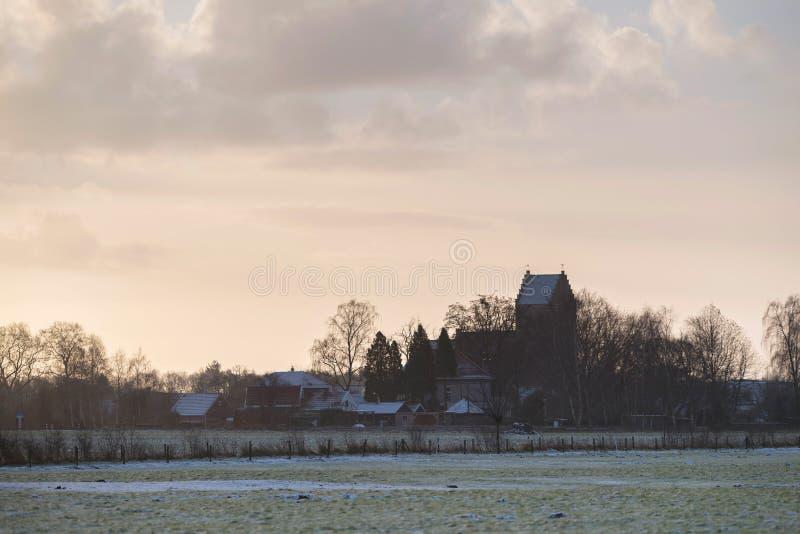 Torre de iglesia vieja del pueblo en paisaje rural del invierno Geesteren foto de archivo libre de regalías