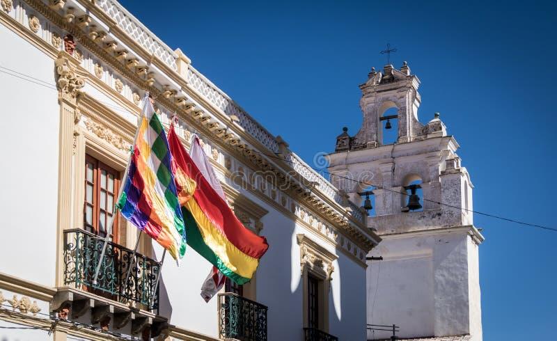 Torre de iglesia y Wiphala y banderas de Bolivia - Sucre, Bolivia foto de archivo