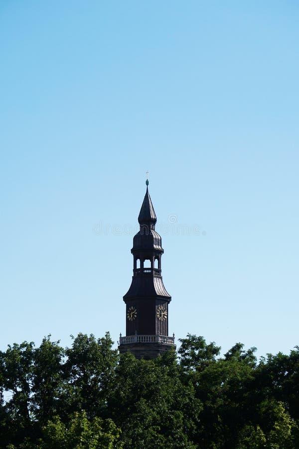 Torre de igreja acima das copas de árvore fotos de stock royalty free