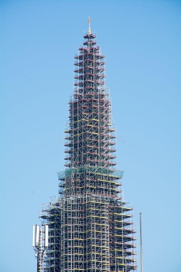 Torre de igreja com o andaime contra o céu azul fotos de stock