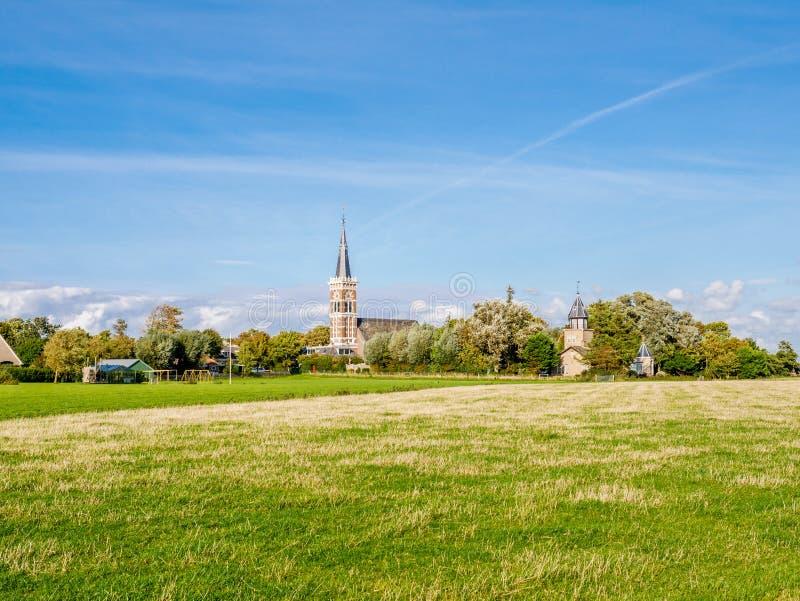 Torre de igreja da vila de Cornwerd e da pastagem na província de fotos de stock