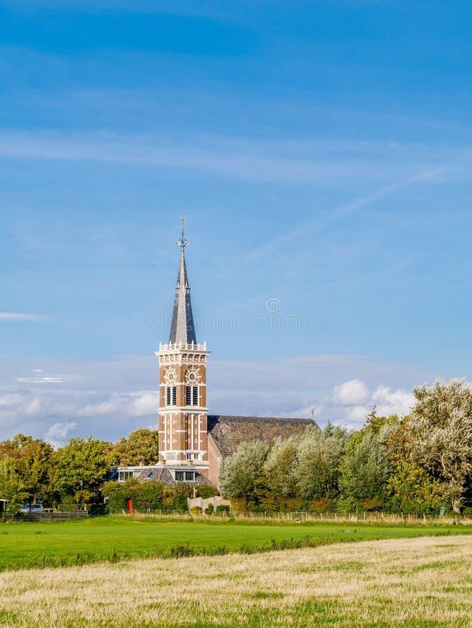 Torre de igreja da vila de Cornwerd e da pastagem na província de foto de stock royalty free