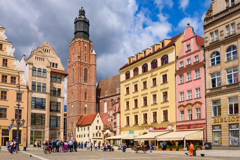Torre de igreja do St Elizabeth e construções coloridas no mercado em Wroclaw foto de stock