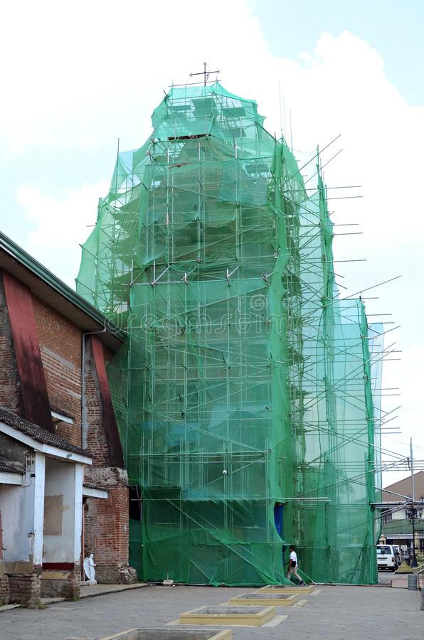 Torre de igreja encoberta na rede e no andaime da construção sob a renovação imagens de stock