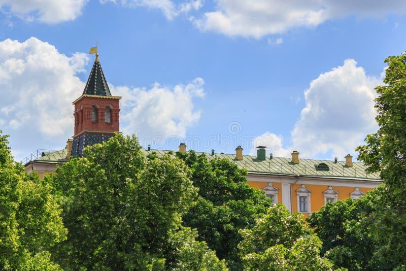 Torre de Komendantskaya do Kremlin de Moscou em um céu azul e em um fundo verde das árvores fotos de stock