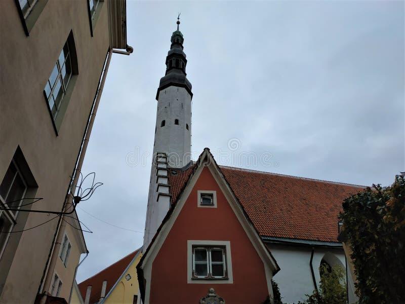 Torre de la iglesia del Espíritu Santo con la casa roja en Tallinn imágenes de archivo libres de regalías