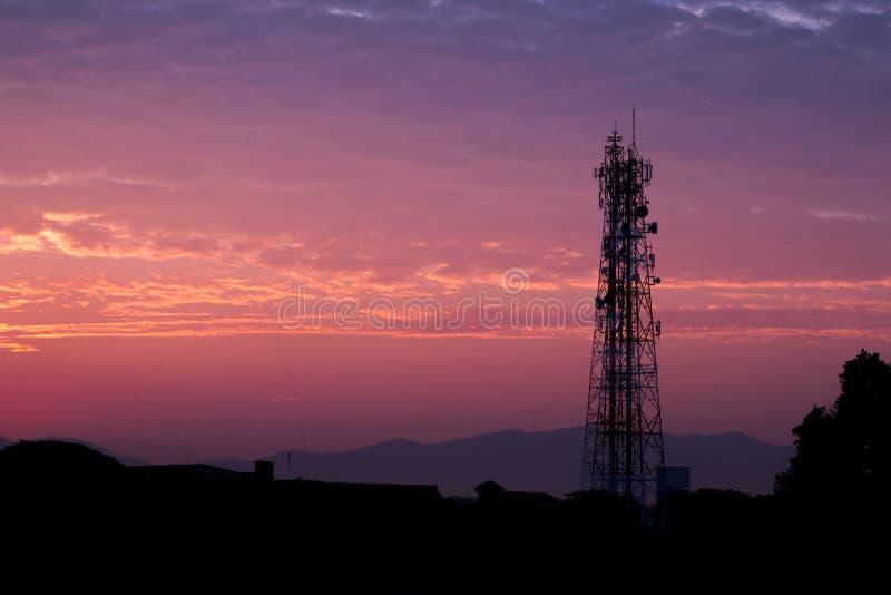 Torre de la telecomunicación de las siluetas en el cielo de la salida del sol y del crepúsculo foto de archivo libre de regalías
