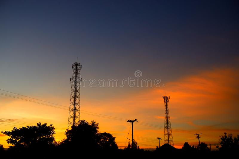Torre de la telecomunicación de las siluetas y polos eléctricos imagen de archivo libre de regalías