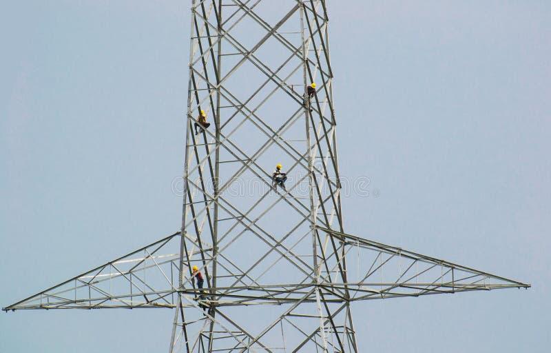 Torre de la transmisión de la electricidad con los trabajadores fotos de archivo