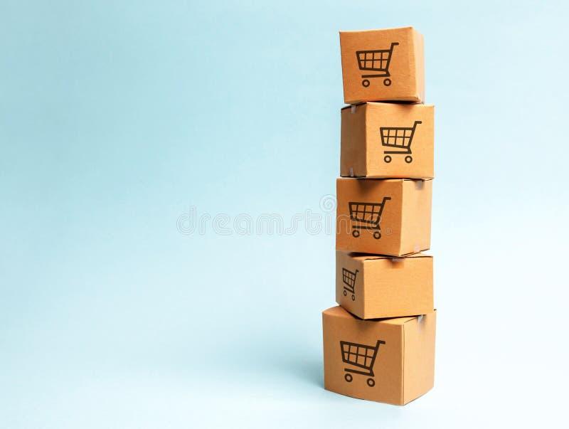 Torre de las cajas de cartón con el modelo de carros de la compra en un fondo azul comercio, compras en línea Poder adquisitivo imágenes de archivo libres de regalías