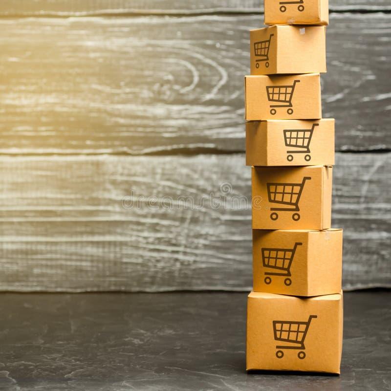 Torre de las cajas de cartón con el modelo de carros de la compra Poder adquisitivo, orden de expedición Comercio electrónico, lo imágenes de archivo libres de regalías