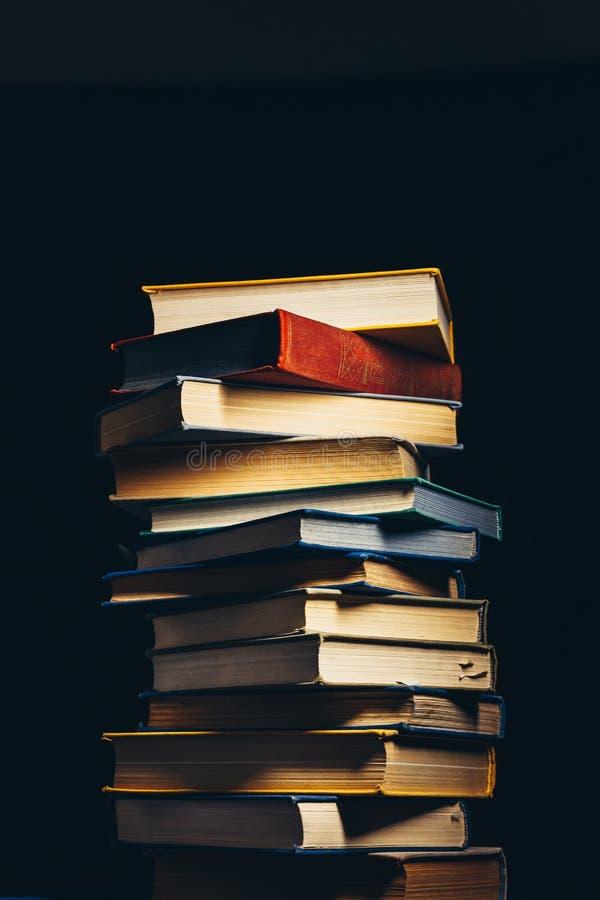 Torre de libros multicolores viejos en un fondo negro Concepto de educación y de conocimiento imagen de archivo libre de regalías