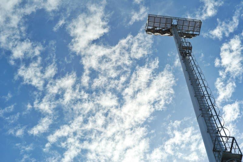 Torre de luzes alta do ponto do estádio com nuvem e o céu azul no fundo Silhueta do polo do aço da luz do ponto imagem de stock
