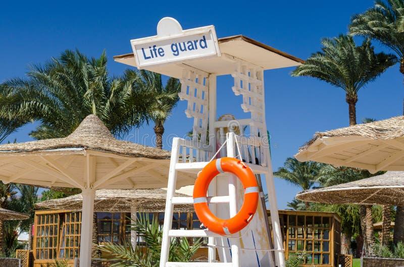 Torre de madera del salvavidas con salvavidas anaranjado en la playa contra el contexto de palmeras y de parasoles de lámina en  fotos de archivo
