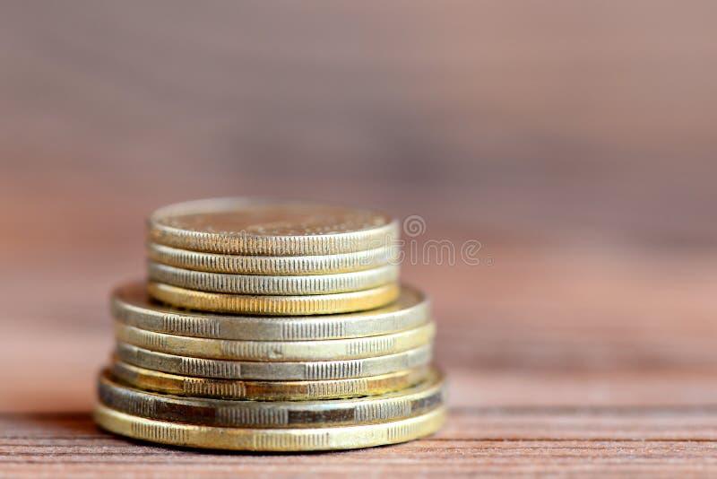 Torre de monedas en un fondo de madera Pluma, lentes y gráficos Dinero primer imágenes de archivo libres de regalías