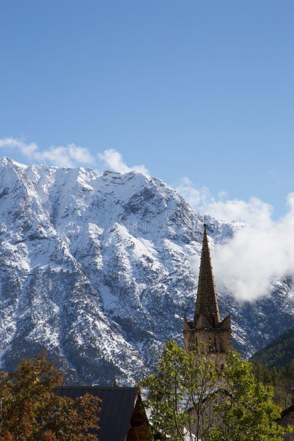 Torre de pedra antiga da igreja com a montanha coberto de neve magnífica no Alsp francês foto de stock royalty free