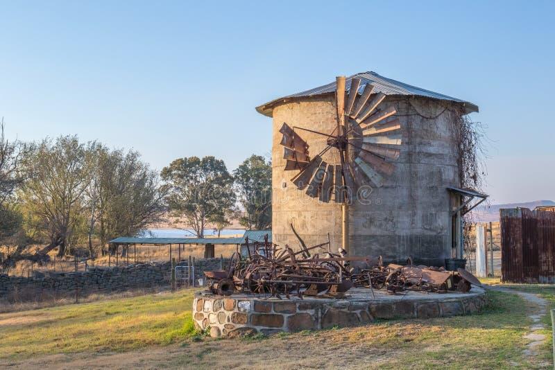 Torre de pedra cinzenta com moinho de vento velho foto de stock