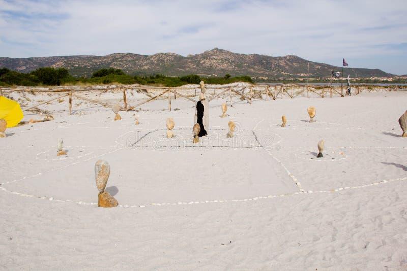 Torre de pedra do zen na praia, com um respingo da onda do mar ao redor Pedras alongadas no equilíbrio no litoral fotografia de stock royalty free