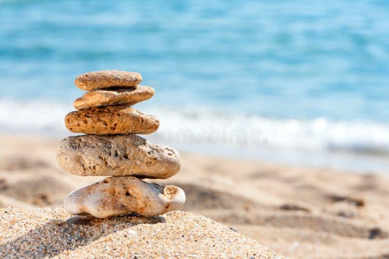 Torre de piedra en arena contra el mar. fotografía de archivo