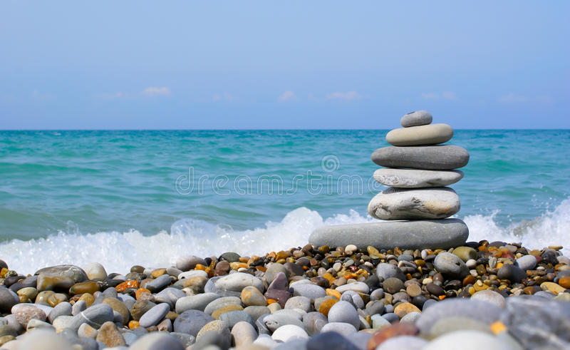Torre de piedra en la playa imagenes de archivo