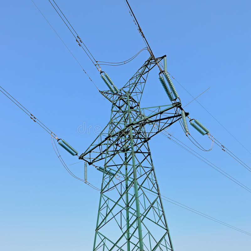 Torre de poder de alta tensão sob o céu azul imagem de stock