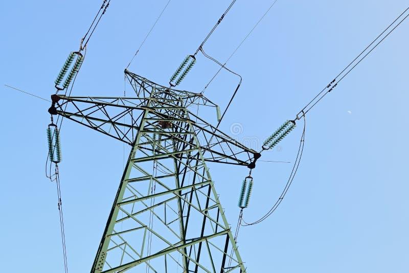 Torre de poder de alta tensão sob o céu azul fotos de stock royalty free