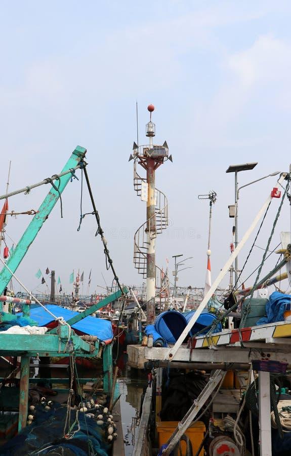 Torre de poste para la luz de señal entre muchos barcos de pesca de Indonesia amarrados en el puerto foto de archivo libre de regalías