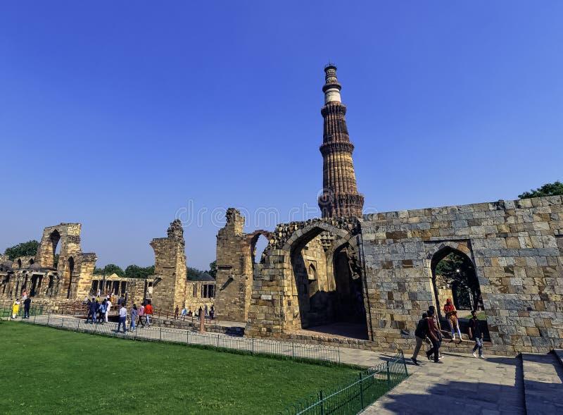 Torre de Qutb Minar vista a través la mezquita arruinada en el complejo de Qutub Minar - Nueva Deli, la India fotografía de archivo